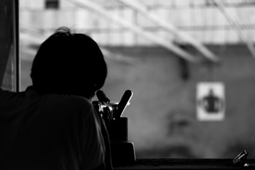 Man shooting a rifle gun to human target processed in black and white colour tone.