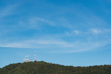 Telecommunication towers with TV antennas and satellite dish on the green hill against blue sky with warm light.