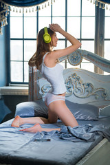 Young girl listening to music with wireless headphones and danci