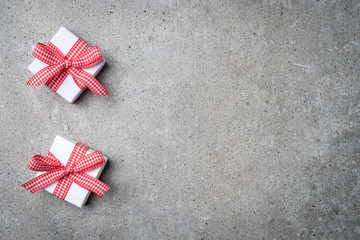 Small gift boxes with red ribbon on gray stone background