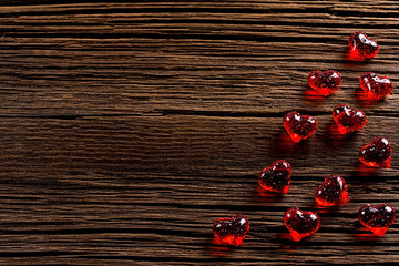 Red hearts made of glass on wooden background.