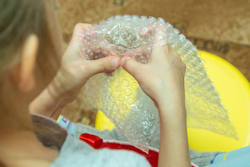 Children's hand pressing the bubbles on the packaging film