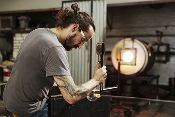 Glassblower with pliers working on piece of glass