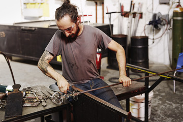 A glassblower working on a shaped piece of glass and using a chisel to shape and finish the object.