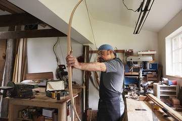 A man testing out a hand made bow by pulling the bow string.