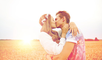 happy young hippie couple kissing in field