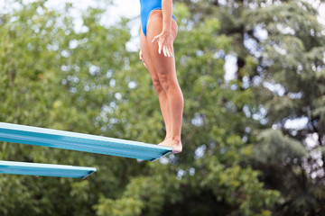 Girl standing on a springboard, preparing to dive in to swimming pool