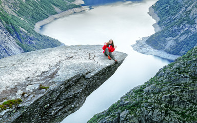 Smiley happy girl sitting at the edge of cliff Trolltunga, over lake Ringedalsvatnet, famous travel destination in Norway. Wanderlust concept.