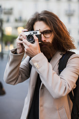 Stylish young man outdoors taking pictures with old-fashioned camera
