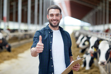 farmer with cows showing thumbs up on dairy farm