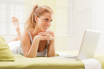 blonde woman using laptop on bed
