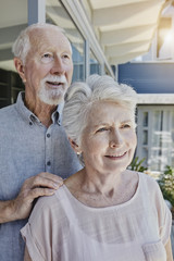 Senoir couple standing in their home, looking confident