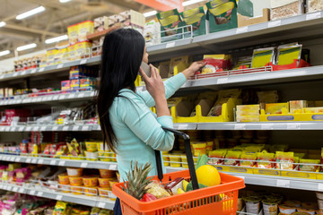 woman with food basket and smartphone at store