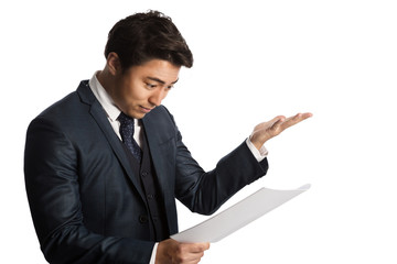 Handsome businessman in a blue suit and tie, standing against a white background with a document in his hand with a very displeased look on his face, feeling angry and unsatisfied.