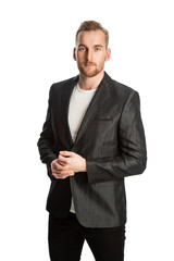 Handsome trendy man in a linen jacket standing against a white background smiling.