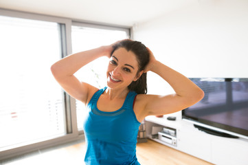 Young woman exercising at home, stretching neck.