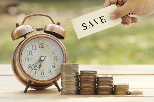 hand holding sign of save on coins and clock on table, concept in save, investment and finace in business