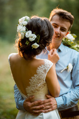 Couple on the nature, the bride and groom hugging at the wedding.