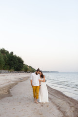 Beach honeymoon couple holding hands walking on white sand beach. Newlyweds happy in love relaxing on summer holidays. Travel vacation concept.