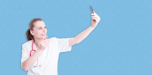 Female doctor in white uniform taking a selfie
