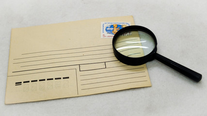 mail envelope postage stamp and magnifying glass