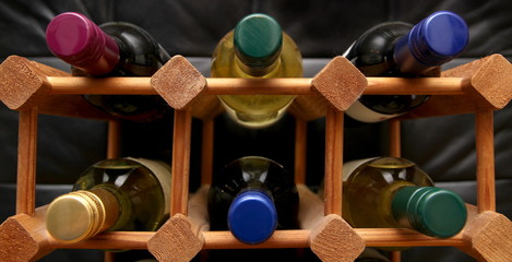 Wooden wine rack with various color bottle tops on dark backgrou