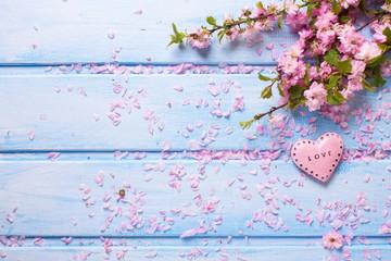 Fresh pink  sakura flowers and  little decorative heart on blue