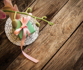 A gift on a white napkin andorchidea on the wooden background