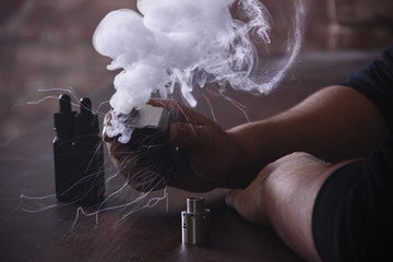 Vaping device in in the man's hand.