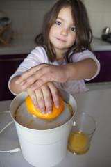 Little girl making orange juice