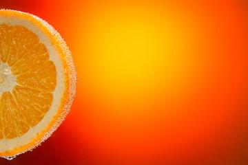 Fresh orange slice in water with bubbles on orange gradient back