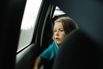 Boy looking out through window while travelling in car