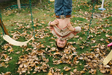 Young boy hanging upside from swing