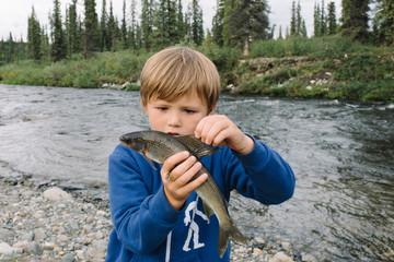 Boy holding fish at national park