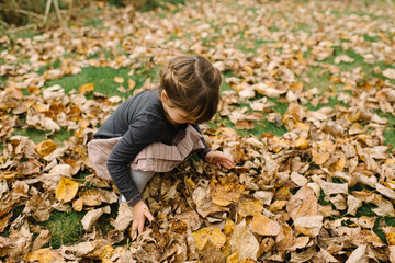Young girl crouching by autumn leaves