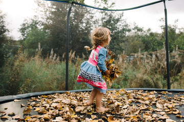 Young girl jumping on trampoline with autumnal leaves