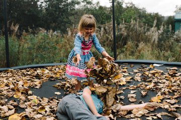 Siblings playing on trampoline with autumnal leaves