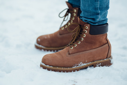 Men's warm winter boots on snow. Brown men's winter boots closeup
