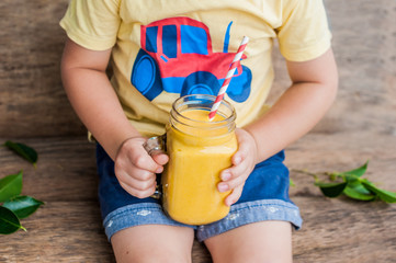 Boy drinking juicy smoothie from mango in glass mason jar with striped red straw on old wooden background. Healthy life concept, copy space