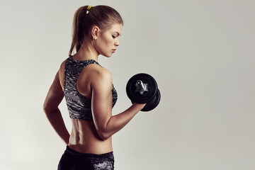 Studio portrait of athletic woman holding dumbbell, improving her arm muscles and body. Copy space on background.