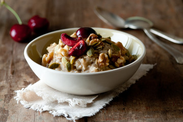 Bowl of fresh oatmeal with pumpkin seeds, walnuts and cherries