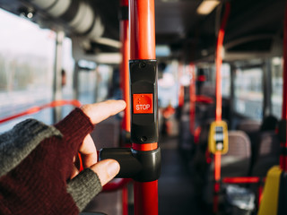 Finger touching the button of stop sign in the autobus