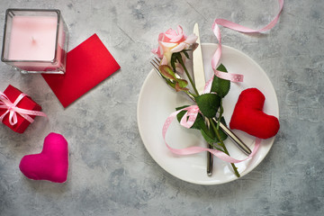Valentines day table setting. Plate silverware heart decorations flower.