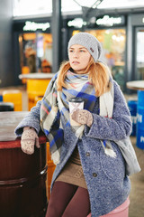 Girl in grey coat, hat and blanket scarf with cup of coffee in cafe in loft industrial style, winter street style lifestyle