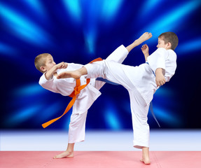 Children athletes beat kicks on a bright blue background