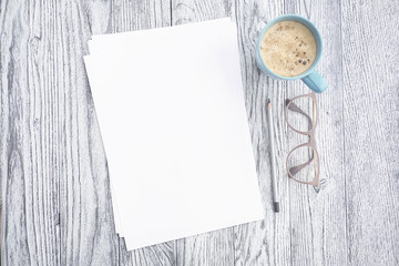 Cup of coffee, glasses, pencil and white sheets of paper on grey wooden background