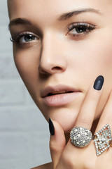 beauty face.woman's hands with jewelry rings.close-up beauty and fashion portrait. girl