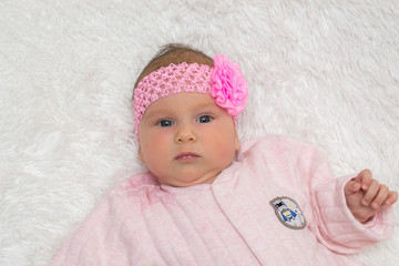 beautiful little kid with a pink bandage on a head lies on a white plaid