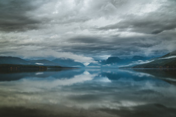 Wall Mural - Overcast skies reflected in a calm lake.