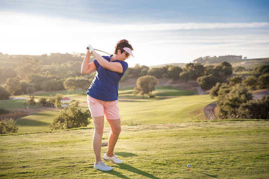 Mature woman playing golf. Golfer hitting golf shot with driver club on course. Beautiful sunny Landscape, green hills, blue sky. Portugal.